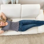 43082931 - young happy woman lying on white sofa at home