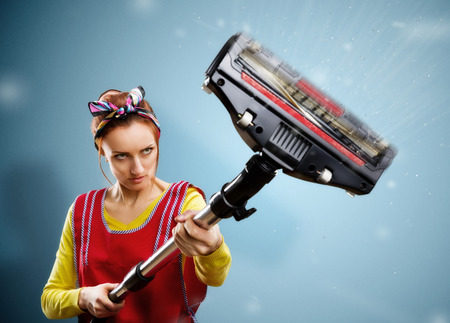 26869972 - housewife with vacuum cleaner isolated on blue