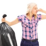 31088301 - woman holding a smelly garbage bag isolated on white background
